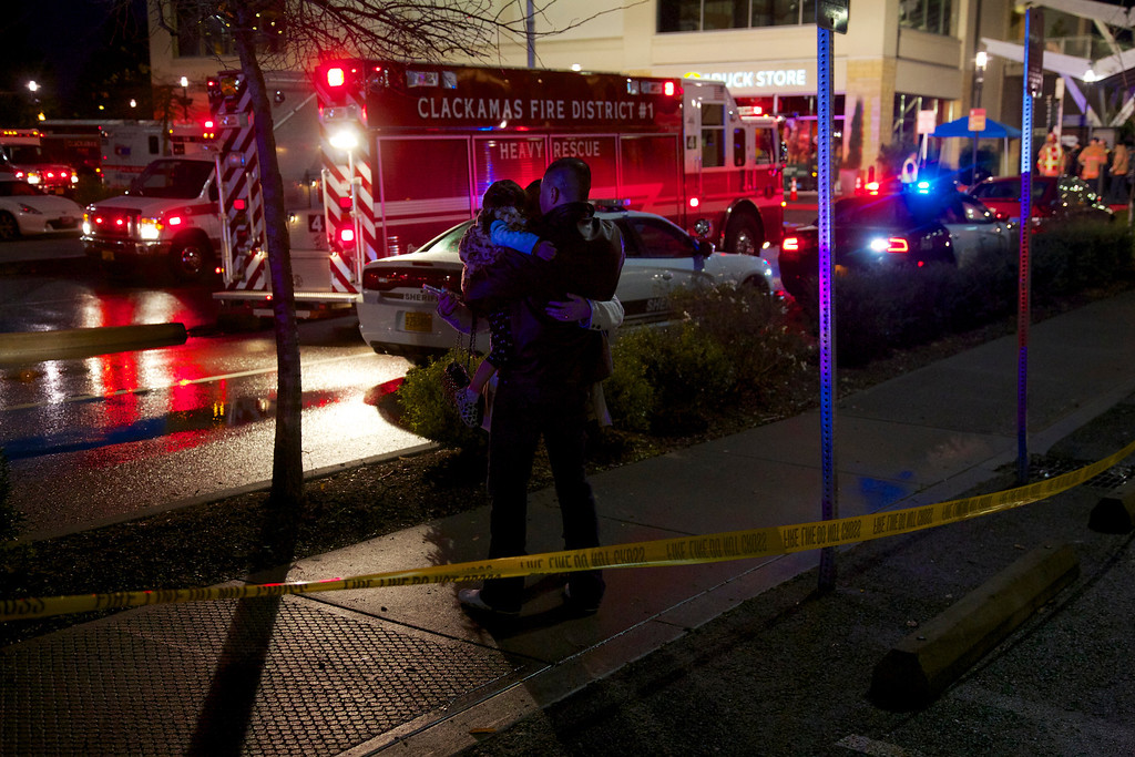 Description of . A couple with a child embrace after they were released from the mall at Clackamas Town Center in Portland, Ore., Tuesday, Dec. 11, 2012. Witnesses say the scene went from cheery to chaotic in seconds when a gunman opened fire in the suburban Portland shopping mall Tuesday, killing two people and wounding another. (AP Photo/The Oregonian, Thomas Boyd)