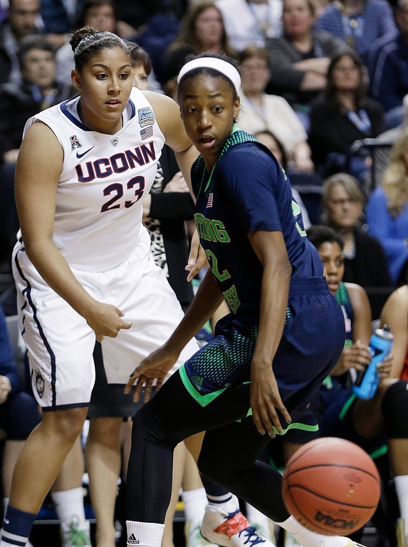 Description of . Connecticut forward Kaleena Mosqueda-Lewis (23) and Notre Dame guard Jewell Loyd (32) vie for a passed ball during the first half of the championship game in the Final Four of the NCAA women's college basketball tournament, Tuesday, April 8, 2014, in Nashville, Tenn. (AP Photo/Mark Humphrey)