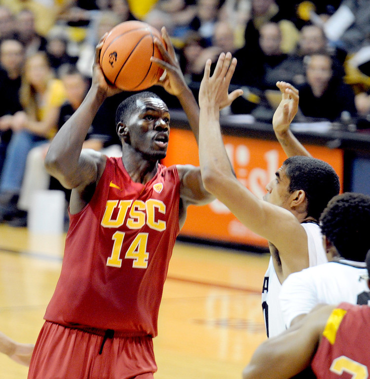 Description of . DeWayne Dedmon of Southern California shoots over Josh Scott of Colorado during the first half of the January 10, 2013 game in Boulder.   Cliff Grassmick/Daily Camera