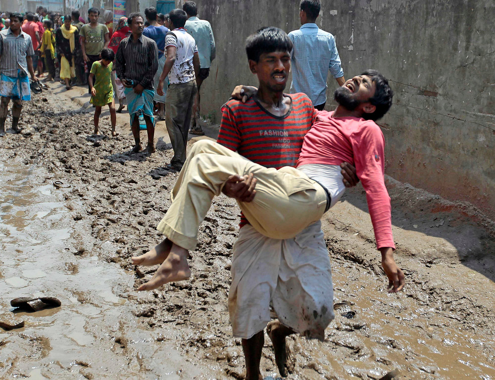 Description of . A survivor reacts in pain as he is carried by a rescuer after an eight-story building housing several garment factories collapsed in Savar, near Dhaka, Bangladesh, Wednesday, April 24, 2013. (AP Photo/ A.M. Ahad)