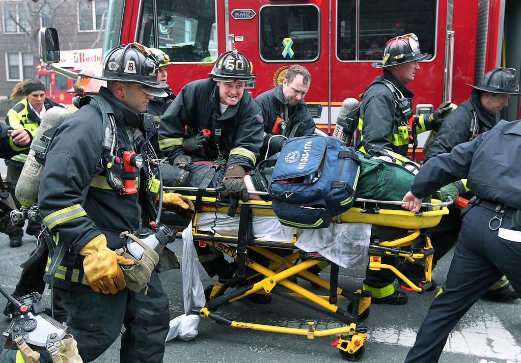 Description of . Firefighters scream for an ambulance as they work on and rush an injured firefighter on a stretcher down Beacon Street, Wednesday, March 26, 2014, in Boston. Firefighters responded to a four-story brownstone fire. A Boston city councilor said two firefighters have died in the fire. (AP Photo/The Boston Globe, Jim Davis)