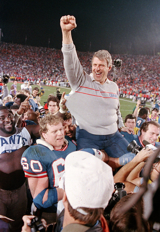 Description of . In this Jan. 25, 1987, file photo, New York Giants coach Bill Parcells is carried off the field after the Giants defeated the Denver Broncos 39-20 in SuperBowl XXI NFL football game in Pasadena, Calif. Parcells moved one step closer to Canton on Saturday, Jan. 7, 2012, when the Pro Football Hall of Fame released a list of 15 modern-era finalists for enshrinement that included the Super Bowl-winning coach. (AP Photo/Eric Risberg, File)