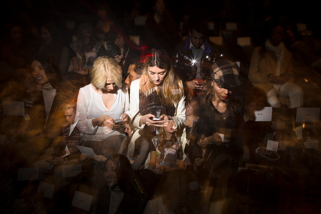 Description of . In this Feb. 7, 2013 photo made with multiple flash exposures, spectators pour over their cell phones while they wait for a show to begin at the Mercedes-Benz Fashion Week tents at Lincoln Center, in New York. (AP Photo/John Minchillo)