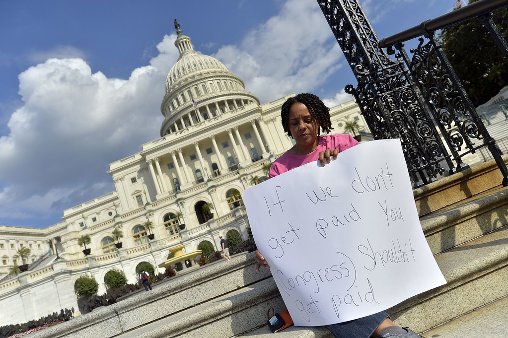 Description of . A protester holds a placard as she joins others in a demonstration in front of the US Capitol in Washington, DC, on October 1, 2013 urging congress to pass the budget bill. US President Obama slammed Republicans for shutting down the government as part of an