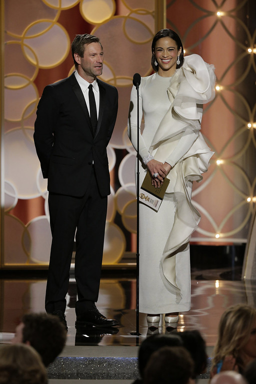 Description of . In this handout photo provided by NBCUniversal, Presenters Aaron Eckhart and Paula Patton speak onstage during the 71st Annual Golden Globe Award at The Beverly Hilton Hotel on January 12, 2014 in Beverly Hills, California.  (Photo by Paul Drinkwater/NBCUniversal via Getty Images)
