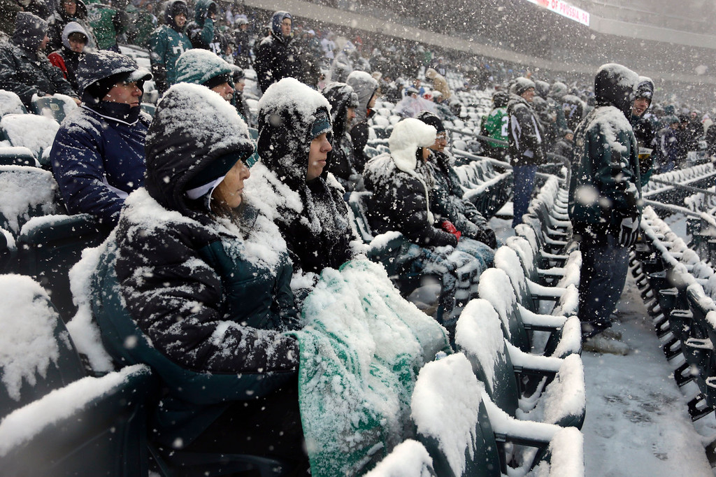 Description of . Fans covered with snow wait in the stands before an NFL football game between the Philadelphia Eagles and the Detroit Lions, Sunday, Dec. 8, 2013, in Philadelphia. (AP Photo/Matt Rourke)