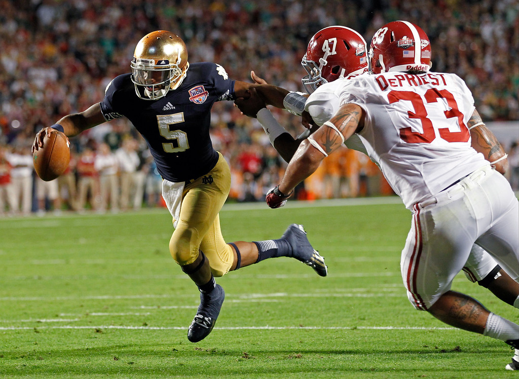Description of . Notre Dame quarterback Everett Golson (5) runs past Alabama's Xzavier Dickson (47) and Trey DePriest (33) for a touchdown during the second half of the BCS National Championship college football game Monday, Jan. 7, 2013, in Miami. (AP Photo/Wilfredo Lee)