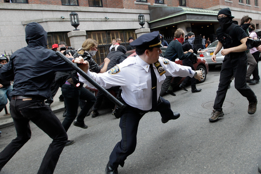 Description of . In this May 1, 2012 file photo, a police lieutenant swings his baton at Occupy Wall Street activists in New York.  Hundreds of activists with a variety of causes spread out over New York City on International Workers Day, or May Day, with Occupy Wall Street members leading a charge against financial institutions. (AP Photo/Mary Altaffer, File)