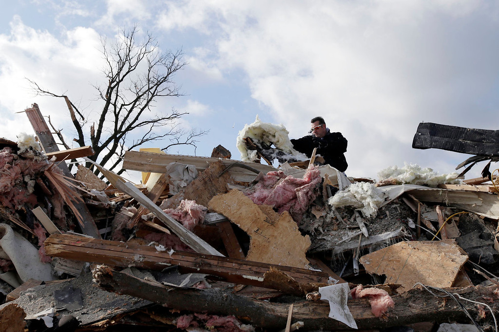 Description of . Allen Rawlins picks through the debris of his parents home, which was destroyed by a tornado, in Kokomo, Ind., Monday, Nov. 18, 2013.  Dozens of tornadoes and intense thunderstorms swept across the U.S. Midwest on Sunday, unleashing powerful winds that flattened entire neighborhoods, flipped over cars and uprooted trees. (AP Photo/AJ Mast)