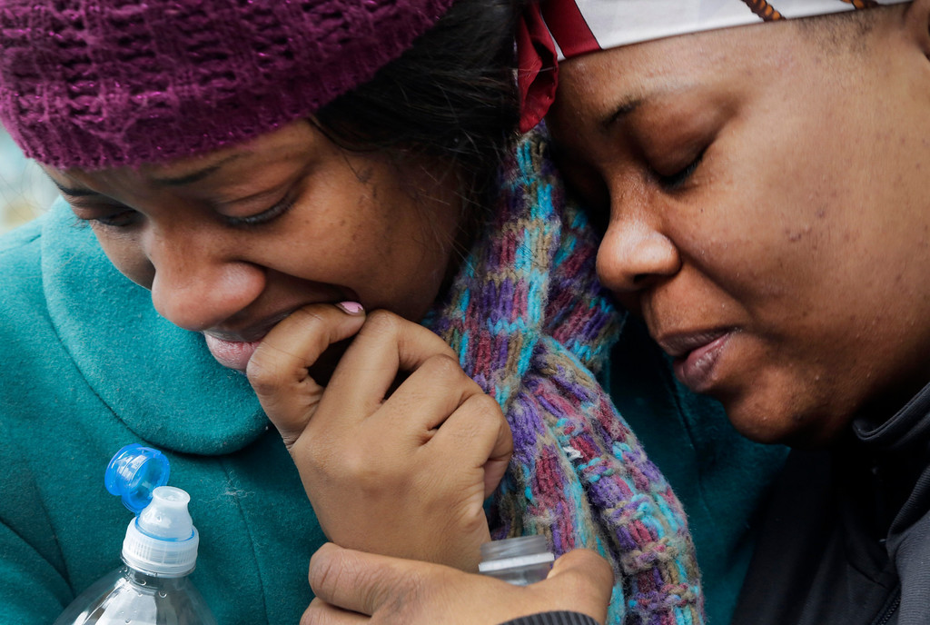 Description of . Alecia Thomas, left, is comforted by her friend, Shivon Dollar, after she lost her home following an explosion that leveled two apartment buildings in the East Harlem neighborhood of New York, Wednesday, March 12, 2014.  (AP Photo/Mark Lennihan)