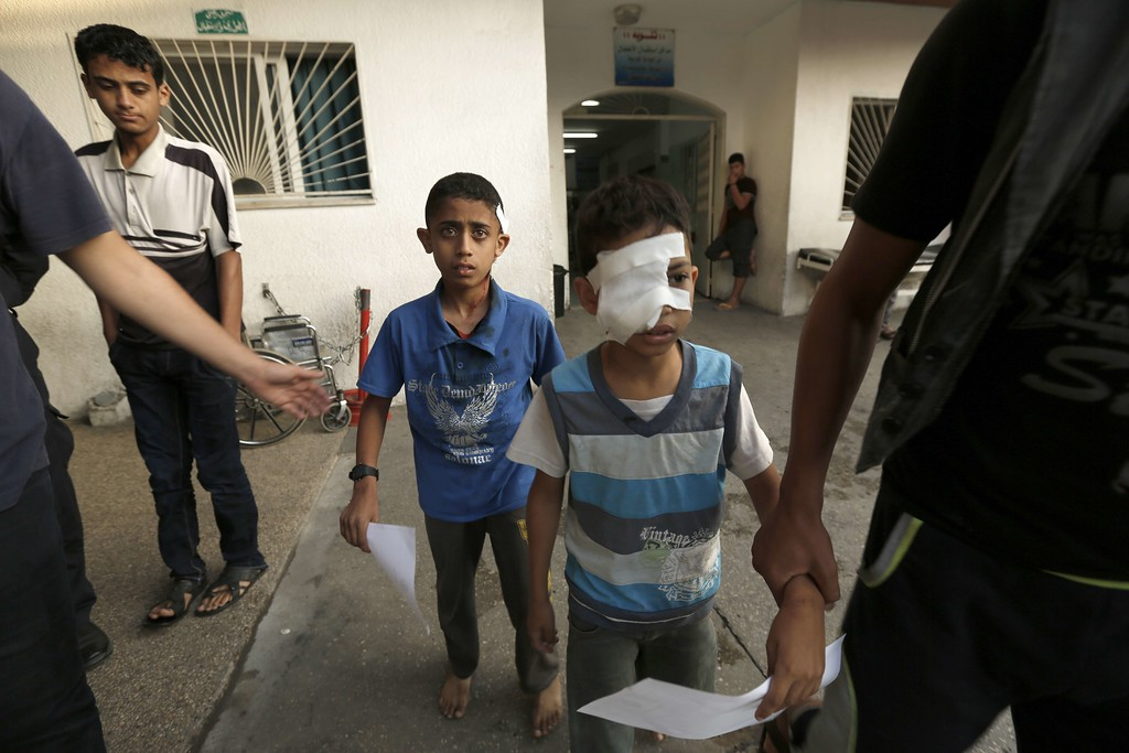 Description of . Two wounded Palestinian children taking shelter at a UN school receive treatment at the Kamal Edwan hospital in Beit Lahia in the northern Gaza Strip early on July 31, 2014. Early in the morning, an Israeli strike attacked a mosque near the same UN school in Jabalia, that was attacked the day before, wounding 15 Palestinians, emergency services said.  AFP PHOTO/ MOHAMMED ABED/AFP/Getty Images