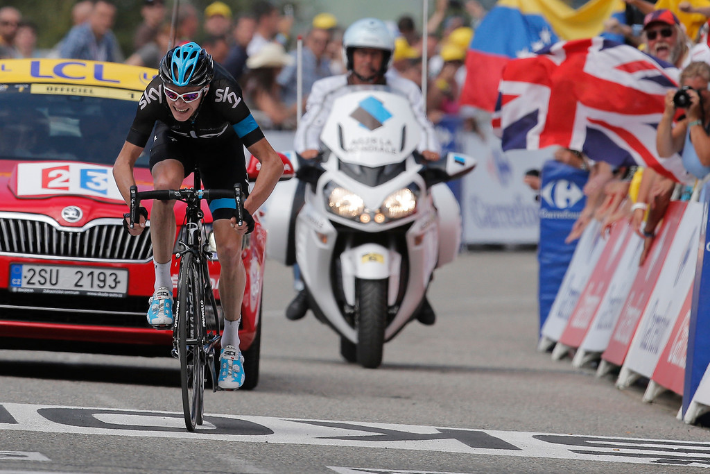 Description of . A fan waves a British flag as new overall leader Christopher Froome of Britain sprints towards the finish line to win the eight stage of the Tour de France cycling race over 195 kilometers (122 miles) with start in Castres and finish in Ax 3 Domaines, Pyrenees region, France, Saturday July 6 2013. (AP Photo/Laurent Cipriani)