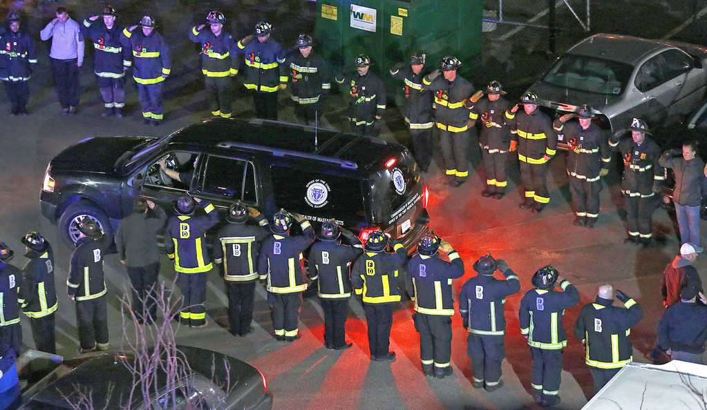 Description of . In this photo made Wednesday night, March 26, 2014, firefighters salute the medical examiner's truck carrying the body of one of two firefighters killed when a fire driven by strong winds whipped through a four-story apartment building in Boston and trapped them in the basement. (AP Photo/Boston Herald, Matt West)