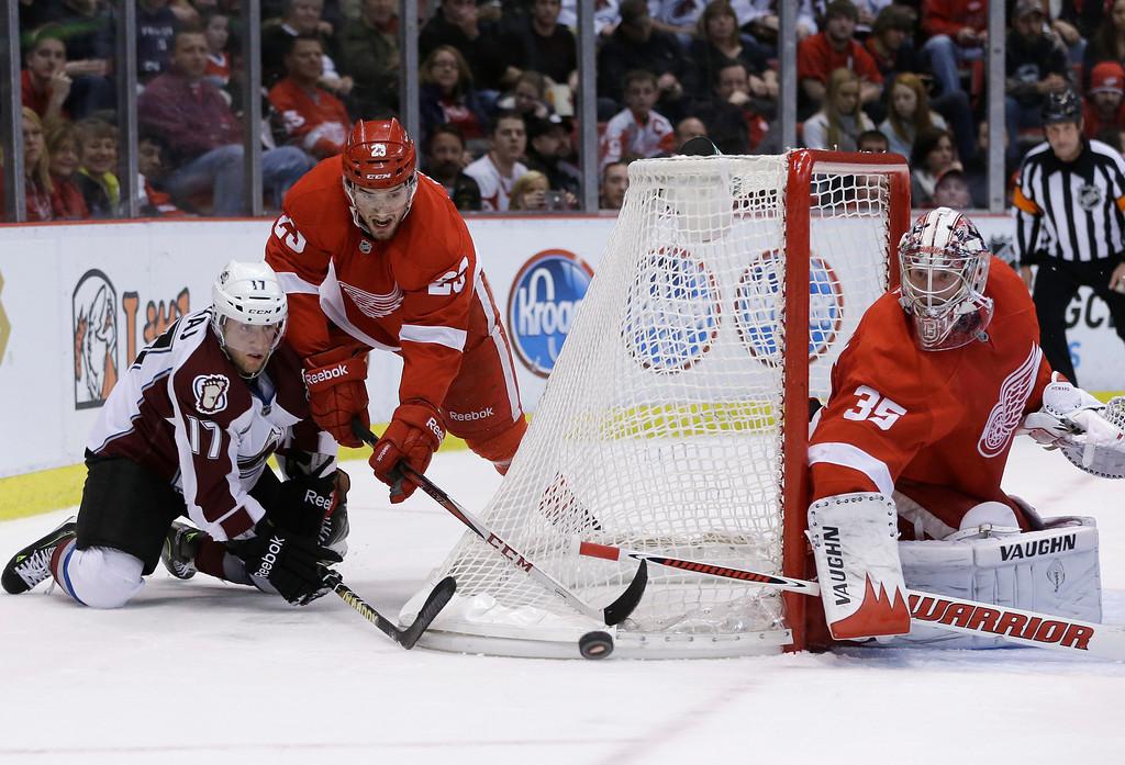 Description of . Colorado Avalanche right wing Aaron Palushaj (17) and Detroit Red Wings defenseman Brian Lashoff (23) reach for the puck behind Detroit goalie Jimmy Howard (35) during the first period of an NHL hockey game in Detroit, Tuesday, March 5, 2013. (AP Photo/Carlos Osorio)