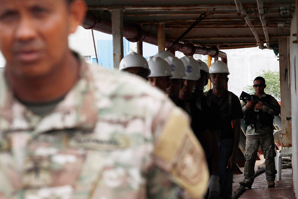 Description of . Police officers stand guards onboard a North Korean flagged ship