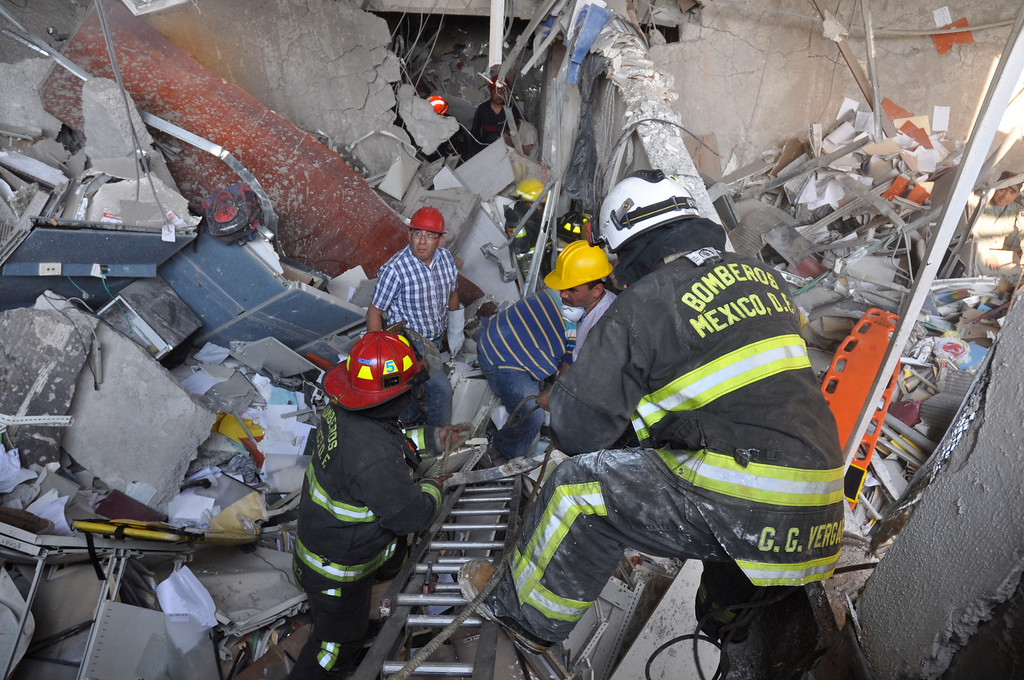 Description of . Firefighters belonging to the Tacubaya sector and workers dig for survivors after an explosion at an adjacent building to the executive tower of Mexico's state-owned oil company PEMEX, in Mexico City, Thursday Jan. 31, 2013. A large explosion occurred in the lower floors of the building and dozens have been reported injured so far. (AP Photo/Guillermo Gutierrez)