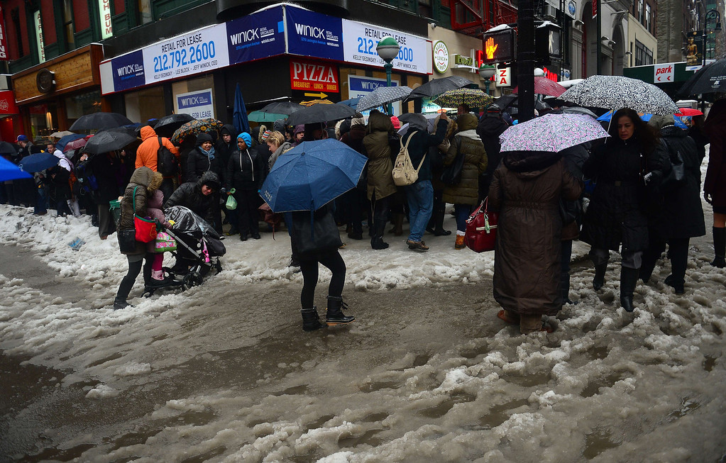 Description of . People cross a street after an overnight snow storm followed by freezing rain in New York, February 5, 2014.  AFP PHOTO/Emmanuel DUNAND/AFP/Getty Images