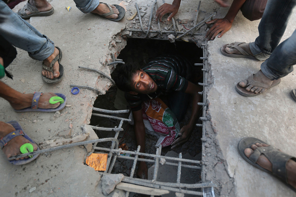 Description of . A Bangladeshi rescuer looks out from a hole cut in the concrete at the site of a building that collapsed Wednesday in Savar, near Dhaka, Bangladesh, Thursday, April 25, 2013. (AP Photo/Kevin Frayer)