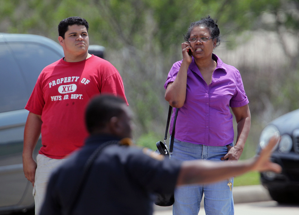 Description of . People wait just off the Lone Star College's Cypress-Fairbanks campus, authorities are reporting least 14 people were hurt in a stabbing at the campus Tuesday, April 9, 2013, in Cypress, Texas.  (AP Photo/Houston Chronicle, James Nielsen)