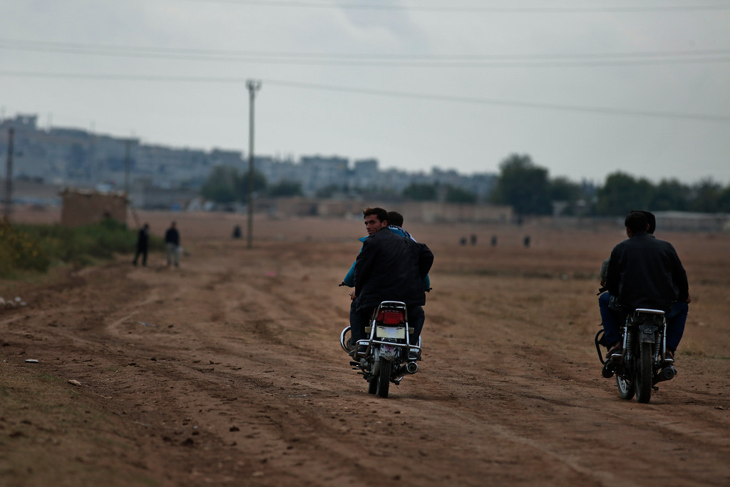 Description of . Syrian Kurdish fighters ride motorcycles on the outskirts of Suruc, on the Turkey-Syria border, as they try to approach the border to cross into Syria to rejoin the fighting In Kobani, background, Friday, Oct. 17, 2014. The are all members of the Peopleís Protection Units, also known as YPG and is fighting against militants of the Islamic State group in Kobani, Syria. According to them, every few weeks, some of the fighters take a couple of days to cross the border into Turkey. Kobani, also known as Ayn Arab, and its surrounding areas, has been under assault by extremists of the Islamic State group since mid-September and is being defended by Kurdish fighters. (AP Photo/Lefteris Pitarakis)