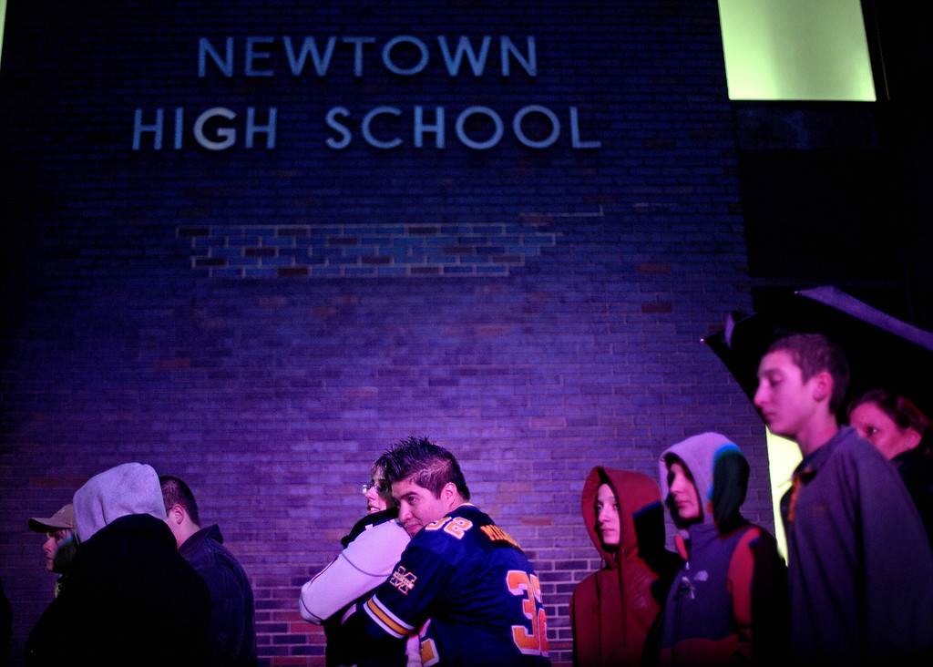 Description of . Josue Gonzales, right, embraces Lindsay Zawesza, as they wait in line to enter Newtown High School for a memorial vigil attended by President Barack Obama for the victims of the Sandy Hook Elementary School shooting, Sunday, Dec. 16, 2012, in Newtown, Conn. A gunman walked into Sandy Hook Elementary School in Newtown Friday and opened fire, killing 26 people, including 20 children. (AP Photo/David Goldman)