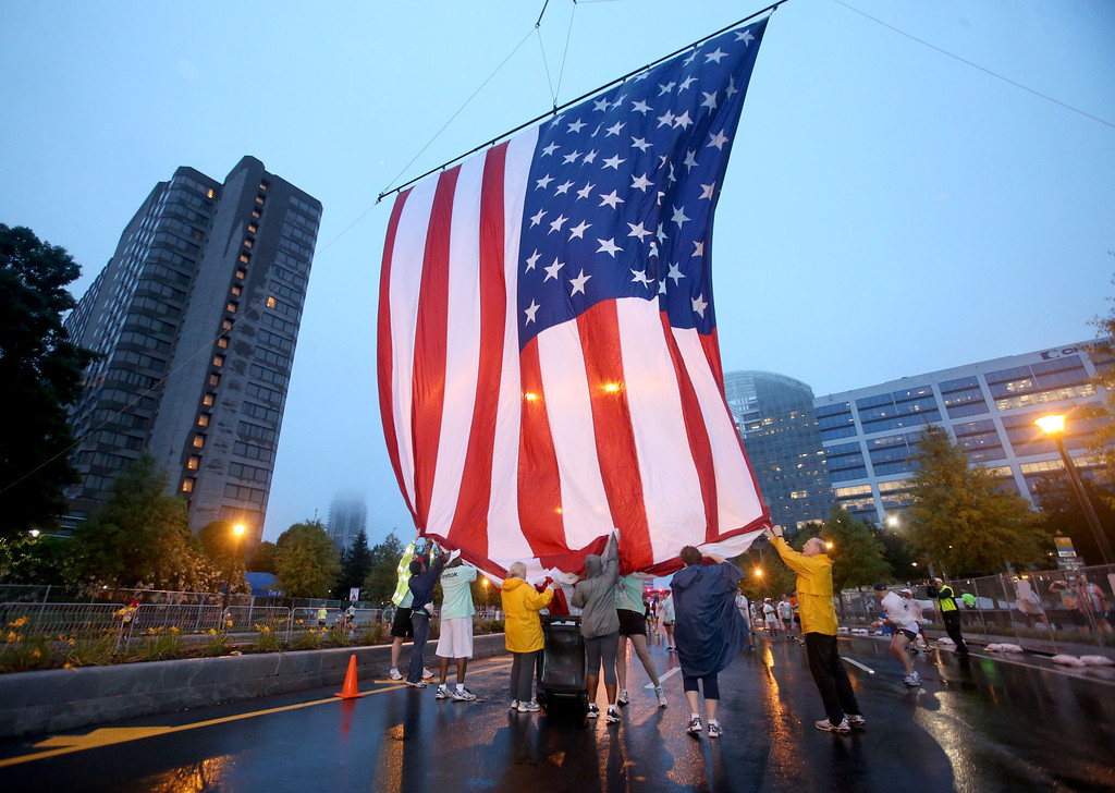 Description of . Volunteers hoist up the U.S. flag at the starting line before the start of the 44th running of the AJC Peachtree Road Race at Lenox Square Thursday morning in Atlanta, Ga., July 4, 2013.  The 10K race is a Fourth of July tradition in Atlanta that's billed as the largest road race in the U.S.  (AP Photo/Atlanta Journal-Constitution,Jason Getz )