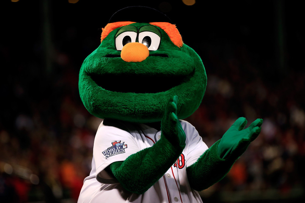 Description of . Wally the Green Monster, mascot of the Boston Red Sox, claps before Game One of the 2013 World Series against the St. Louis Cardinals at Fenway Park on October 23, 2013 in Boston, Massachusetts.  (Photo by Jamie Squire/Getty Images)