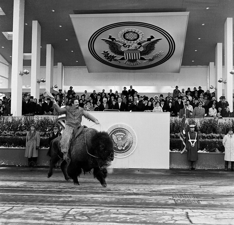 Description of . A man rides a buffalo and draws laughter and applause from spectators in the Presidential reviewing stands, January 20, 1961 in Washinton, D.C. Lyndon Johnson, new Vice-president is seen clapping his hands. President Kennedy's father, Joseph P. Kennedy, stands beside him. (AP Photo)