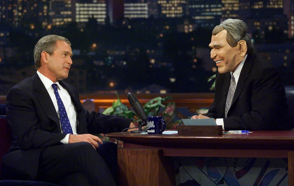 Description of . US Republican Presidential candidate Texas Governor George W. Bush(L) looks over at Jay Leno(r) as he wears a George W. Bush mask as they clown around for upcoming Halloween  as Republican presidential candidate George W. Bush appears on the Tonight Show with Jay Leno late 30 October 2000 in Los Angeles,CA.  (PAUL J. RICHARDS/AFP/Getty Images)