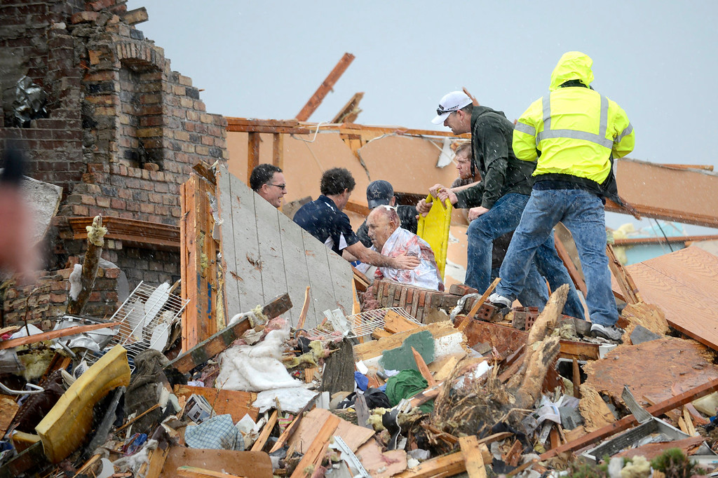 Description of . Rescuers pull an injured resident from a demolished house after a tornado destroyed parts of Washington, Ill., Sunday, nov. 17, 2013. (AP Photo/Journal Star, David Zalaznik)