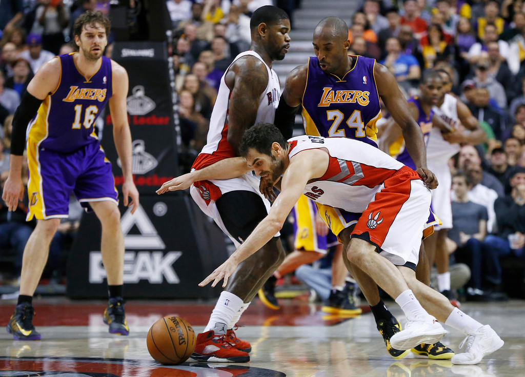Description of . Toronto Raptors' Jose Calderon (bottom R) drives as teammate Amir Johnson (C) sets a pick on Los Angeles Lakers' Kobe Bryant (24) during the second half of their NBA basketball game in Toronto, January 20, 2013.     REUTERS/Mark Blinch