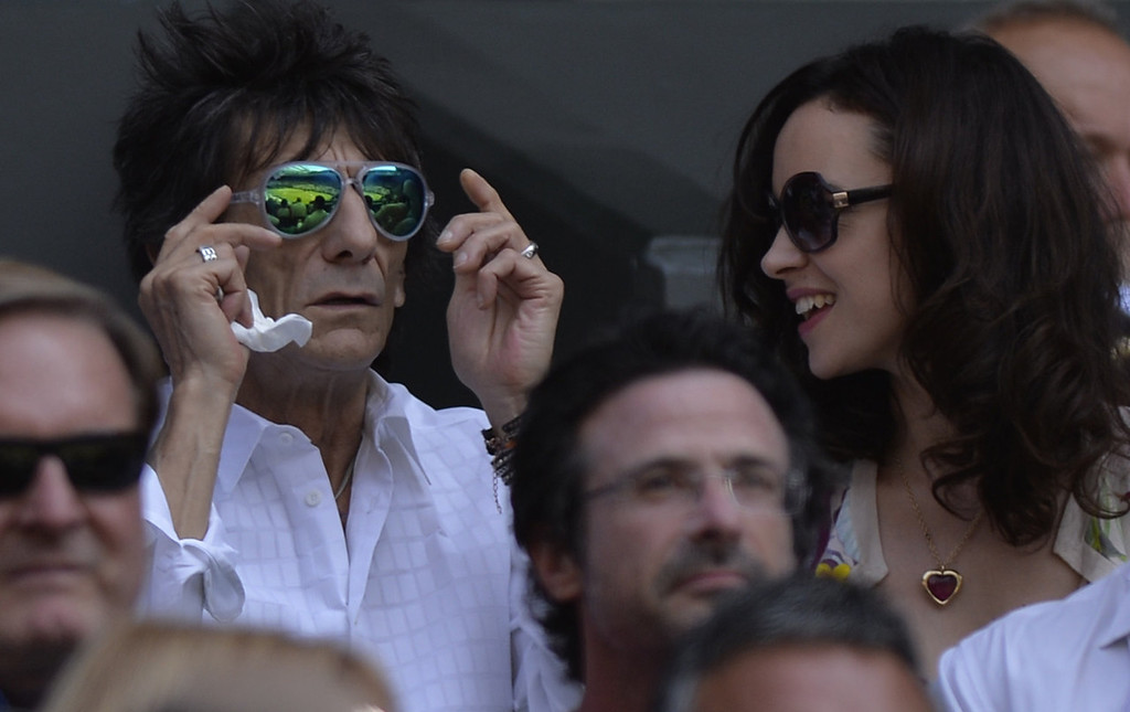 Description of . British musician Ronnie Wood of The Rolling Stones (L) sits with his wife Sally Humpheys in the crowd watching the men's singles final between Serbia's Novak Djokovic and Britain's Andy Murray on day thirteen of the 2013 Wimbledon Championships tennis tournament at the All England Club in Wimbledon, southwest London, on July 7, 2013.  ADRIAN DENNIS/AFP/Getty Images