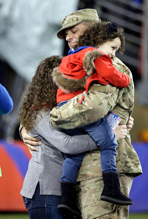 Description of . Air Force Tech. Sgt. David H. Brenhuber, of Cherry Hill, N.J., who is serving in Afghanistan, hugs his wife and daughter for a surprise reunion during the first half of an NFL football game between the New York Giants and the Green Bay Packers, Sunday, Nov. 17, 2013, in East Rutherford, N.J. (AP Photo/Seth Wenig)