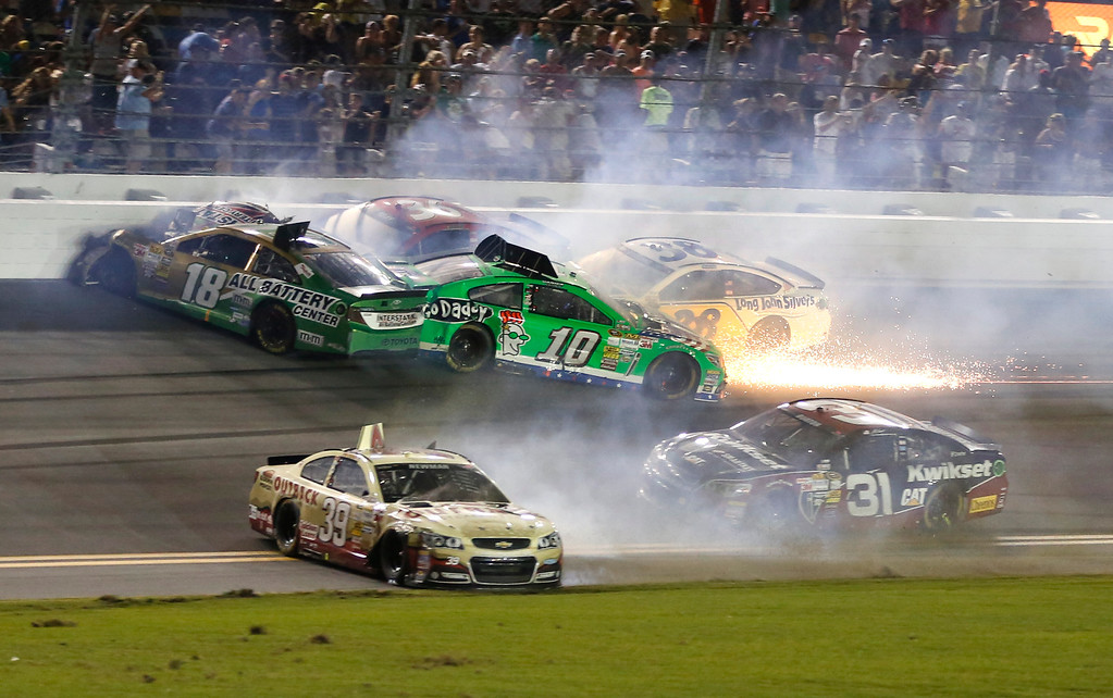 Description of . Cars wreck on the front stretch including Kyle Busch (18), Danica Patrick (10), Ryan Newman (39),  David Gilliland (38), and Jeff Burton (31) on the last lap of the NASCAR Sprint Cup auto race at Daytona International Speedway, Saturday, July 6, 2013, in Daytona Beach, Fla. (AP Photo/Reinhold Matay)