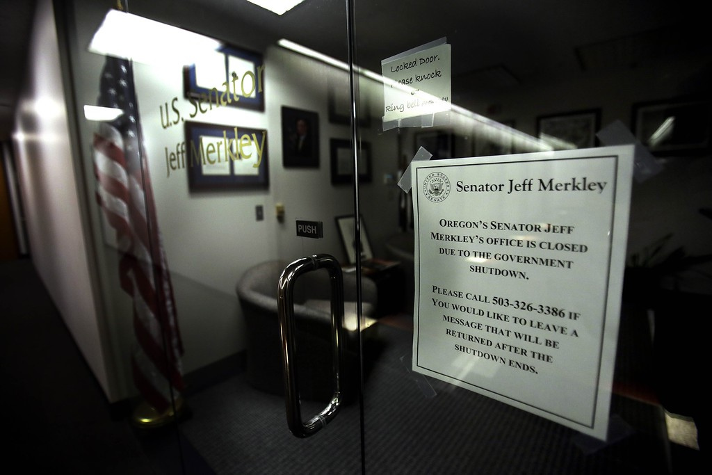 Description of . A sign is posted next to the door to the darkened offices of Sen. Jeff Merkley, D-Ore., in Portland, Ore., Wednesday, Oct. 2, 2013. The government shutdown is in its second day.(AP Photo/Don Ryan)