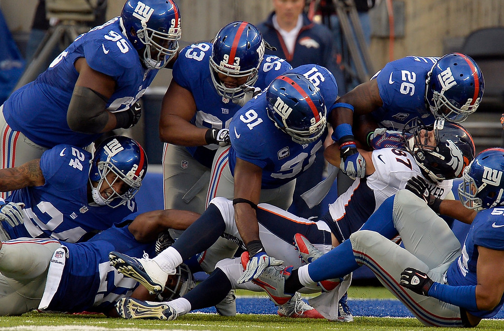 Description of . Denver Broncos wide receiver Eric Decker (87) gets wrapped up by the New York Giants defense at the 2 yard line during the third quarter September 15, 2013 MetLife Stadium. (Photo by John Leyba/The Denver Post)