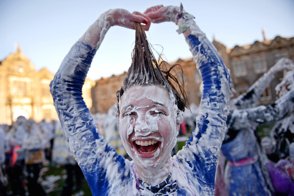 . Students from St Andrew\'s University indulge in a tradition of covering themselves with foam to honour the \'academic family\' on November 4, 2013, in St Andrews, Scotland. Every November the \'raisin weekend\' which is held in the university\'s St Salvator\'s Quadrangle, is celebrated and a gift of raisins (now foam) is traditionally given by first year students to their elders as a thank you for their guidance and in exchange they receive a receipt in Latin.  (Photo by Jeff J Mitchell/Getty Images)