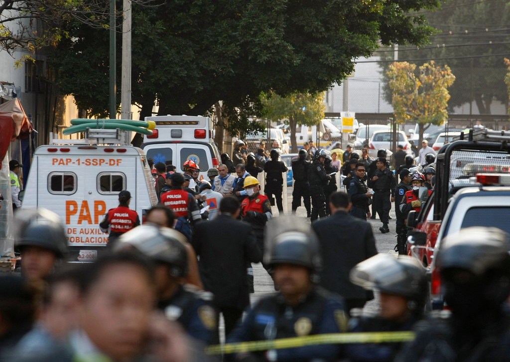 Description of . Ambulances and rescue personnel are seen on a street outside the headquarters of state oil giant Pemex in Mexico City January 31, 2013. A powerful explosion rocked the Mexico City headquarters of Pemex on Thursday, killing at least 14 people and injuring 100 others.    REUTERS/Bernardo Montoya