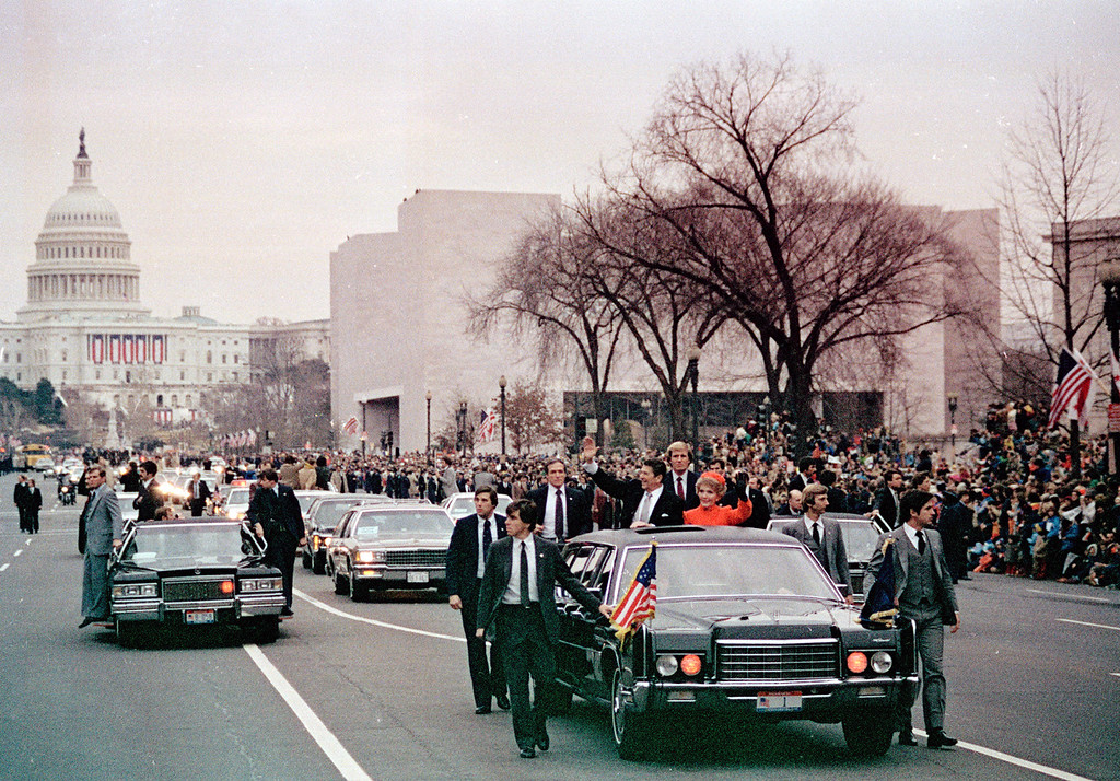 Description of . U.S. President Ronald Reagan, left, and first lady Nancy Reagan wave to the crowd from their limousine as they lead the motorcade down Washington's Pennsylvania Avenue on inauguration day, Jan. 20, 1981, following swearing-in ceremony. The Capitol building is visible in background, left. (AP Photo)