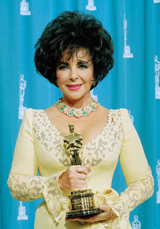 Description of . FILE - In this March 29, 1993 file photo, actress Elizabeth Taylor displays the Jean Hersholt Award she received at the 65th Annual Academy Awards in Los Angeles, Calif.  The FBI in 1949 investigated three threatening letters sent to the then-17-year-old actress after receiving complaints from Taylor's parents about obscene letters sent to the up-and-coming star. At the time, investigators had to manually compare handwriting samples and postmarks, but many modern stalking cases involve examining digital fingerprints obsessed fans leave online when targeting their celebrity victims. (AP Photo/Reed Saxon, file)