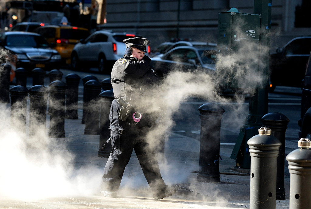 Description of . A police officer walks past a steam grate in Lower Manhattan Borough of New York, New York, USA, 07 January 2013. Many parts of the United States are experiencing record cold temperatures due to an usual polar vortex of arctic air.  EPA/ANDREW GOMBERT