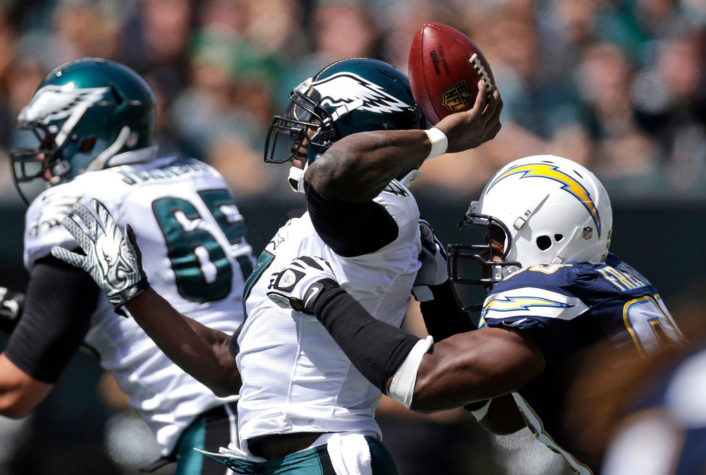 Description of . Philadelphia Eagles\' Michael Vick, left, tries to pass as he is hit from behind by San Diego Chargers\' Dwight Freeney during the first half of an NFL football game, Sunday, Sept. 15, 2013, in Philadelphia. (AP Photo/Matt Rourke)