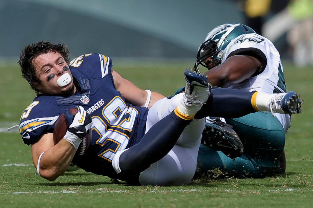 Description of . San Diego Chargers' Danny Woodhead, left, loses his helmet as he is tackled by Philadelphia Eagles' DeMeco Ryans during the first half of an NFL football game on Sunday, Sept. 15, 2013, in Philadelphia. (AP Photo/Michael Perez)