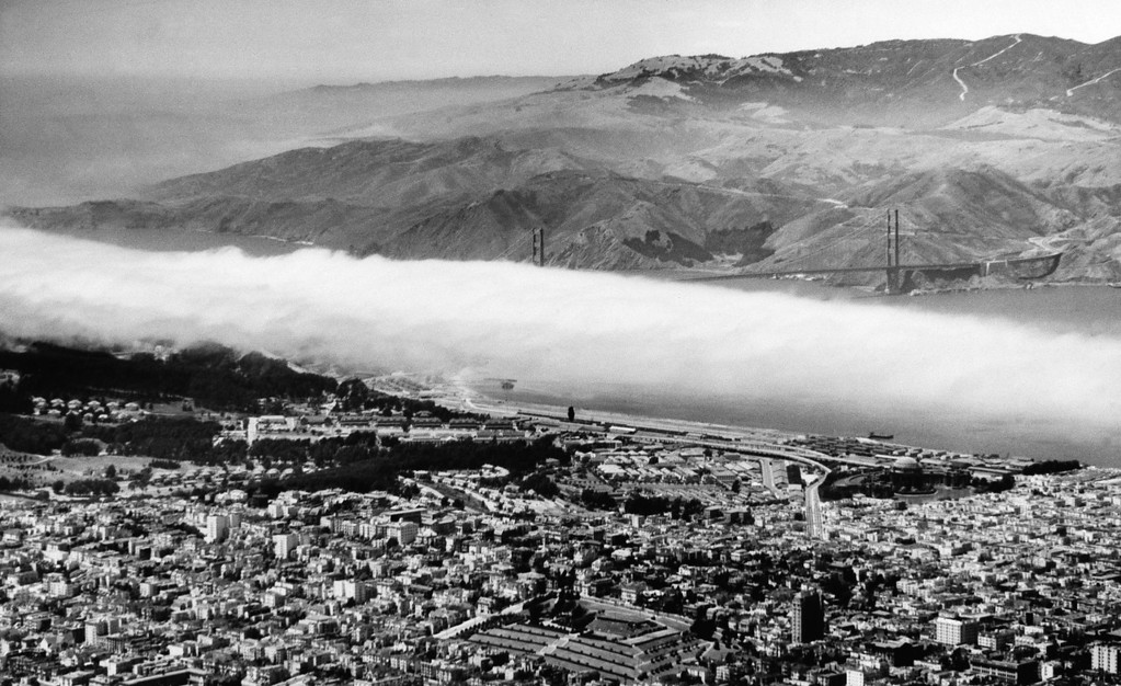 Description of . San Francisco is resting comfortable on June 5, 1949 after a hot 4th of July holiday. With the Marin County hills in the background, the Golden Gate Bridge is partially obscured by the fog blanket. The incoming fog lowered the temperature by 23 degrees to a comfortable 69. (AP Photo)