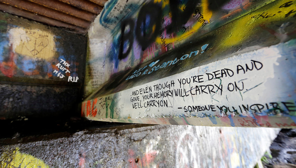Description of . In this photo taken Monday, Sept. 23, 2013, graffiti, mostly written about Kurt Cobain, the late frontman of Nirvana, adorns the underside of the Young Street Bridge blocks from his childhood home in Aberdeen, Wash.  (AP Photo/Elaine Thompson)
