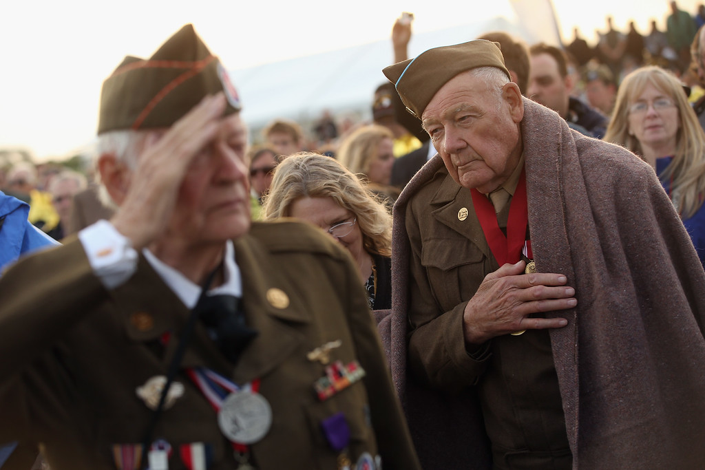 Description of . D-day veterans Frederick Carrier (L), 89, and James McDonald Hamby, 90 of Lenoir, North Carolina, listen to the playing of the U.S. national anthem at the U.S. Ceremony on June 5, 2014 at Utah Beach, France.   (Photo by Sean Gallup/Getty Images)
