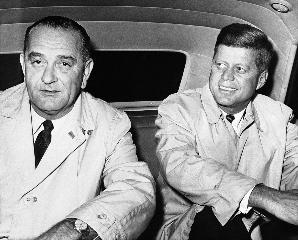 Description of . Sen. Kennedy and running mate Sen. Lyndon Johnson sit in a car outside hotel Biltmore in New York, Nov. 5, 1960. Associated Press file