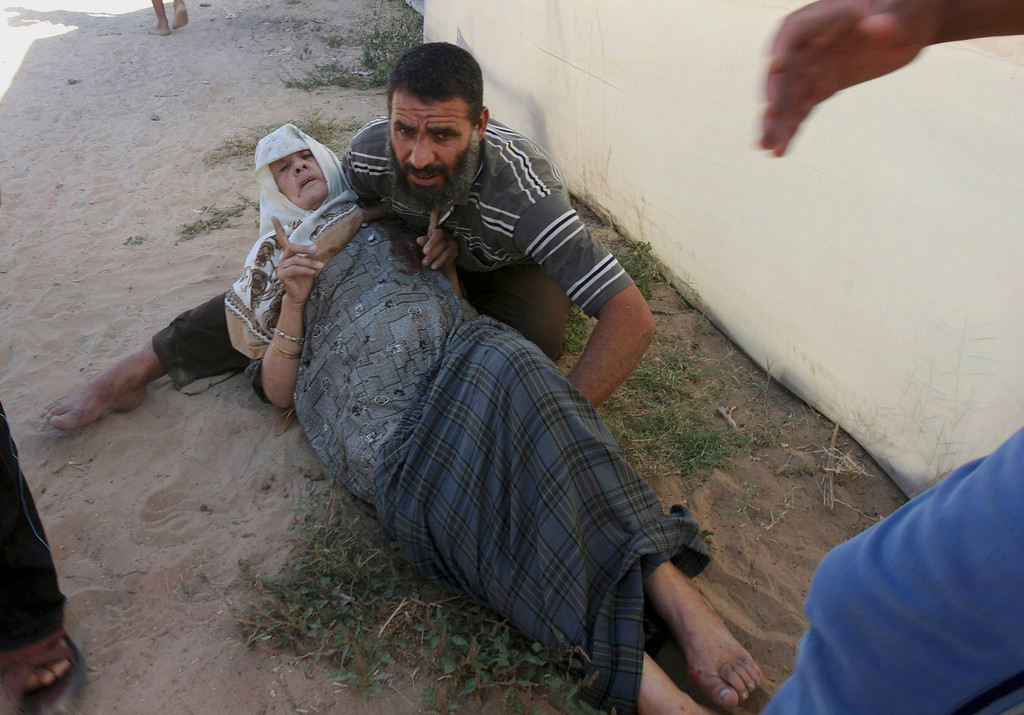 Description of . A Palestinian relative helps a wounded woman following an Israeli air strike on a building in Khan Younis in the southern Gaza Strip, Wednesday, July 30, 2014. (AP Photo/Eyad Baba)