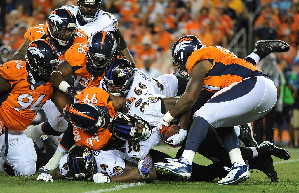 Description of . A host of Denver Broncos defenders bottle up Baltimore Ravens running back Bernard Pierce in the second quarter at Sports Authority Field at Mile High on September 5, 2013. (Photo by Steve Nehf/The Denver Post)