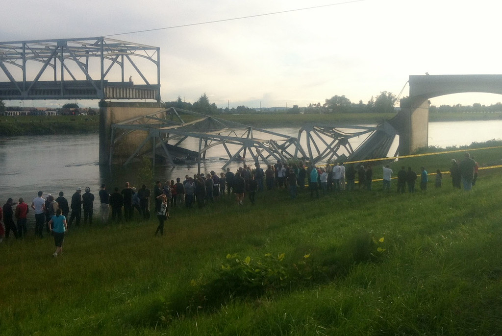 Description of . In this photo provided by NWCN, people look on after the Interstate 5 bridge collapsed over the Skagit River in Skagit County, Wash., Thursday, May 23, 2013. The four-lane bridge over the Skagit River collapsed about 7 p.m., Trooper Mark Francis said. There was no immediate estimate of how many people were in the water or whether there were any injuries or deaths, he said. (AP Photo/NWCN, Selina Dziura)